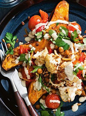 Roasted sweet potato with cauliflower, cherry tomatoes, caramelised garlic and spiced chickpeas