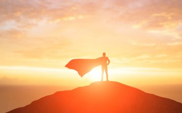 Man standing on top of the mountain in a superhero cape with the sun shining in the background