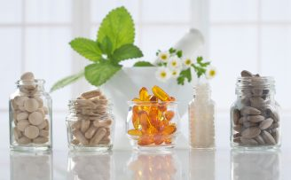 Five bottles of complementary medicines in front of a pestle and mortar