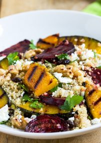 charred pumpkin wedges in a beetroot and quinoa salad served on a white plate