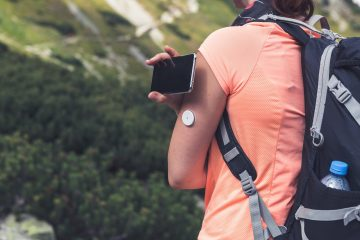 Young woman wearing an orange tshirt using a CGM reader while hiking