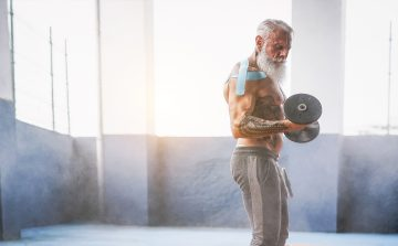 trendy senior bodybuilder with tattoo carrying dumbbell
