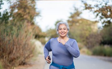 SLightly overweight, happy, grey haired woman jogging down a country road