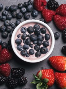 blueberry yoghurt surrounded by strawberries, blueberries and blackberries