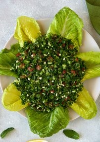 tabbouleh on lettuce leaves on a white plate with two lemon wedges