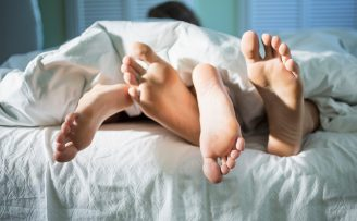 Entwined feet of a young couple in bed