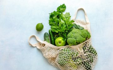 healthy green veg in a string bag against a blue background