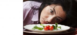 Woman slumps next to a plate of salad.