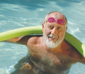 Man in the pool with a noodle and goggles