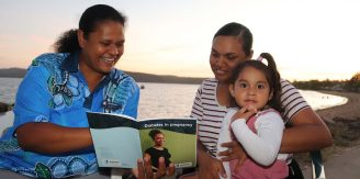 First Nations' health worker reads from a pregnancy booklet with First Nations mum with young child on her knee.