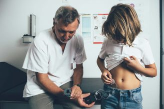 A doctor checks the CGM of a child with diabetes