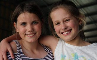 two young girls with type 1 diabetes smiling and embracing with their arms around eachother