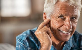 smiling older man touching his ear
