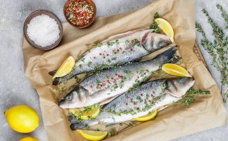 three raw fish in baking tray with lemon and thyme